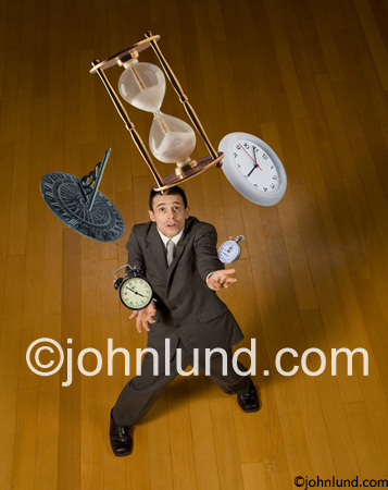 A businessman juggles time in the form of an alarm clock, a clock, a stop watch, as sun dial and an hourglass in a stock photo about work, time management and deadlines.