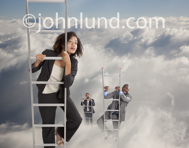 Three ethnically diverse business people climb ladders up through the clouds in their quest for success.