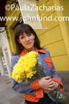 Photo of a woman holding a bouquet of yellow flowers as she walks down the sidewalk. She has shoulder length brown hair and a colorful blue and orange jacket.  Red fingernail polish. Happy hispanic woman with flowers.