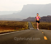 Photo of a woman running on a long straight highway in the American South West in a metaphor for determination, perseverance and dedication.