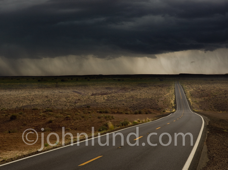 A picture of the road to success either coming or going through a storm, a rain squall, on the distant horizon.