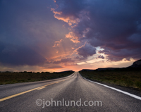 A long road stretches through the desert as a sunrise lights up the storm clouds above.