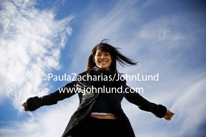 Camera below woman looking up at her. Woman with shoulder length hair wearing a black coat and smiling down at the camera from above. Wispy white clouds in a blue sky framing her.