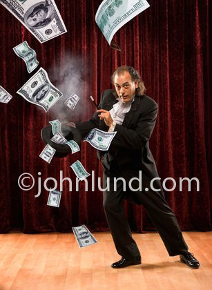 A magician waves his magic wand producing a flow of cash in the form of hundred dollar bills to come flying out of his top hat in a demonstration of easy money.