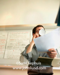 Stock photo of a man drinking a cup of coffee and holding some paperwork in his other hand. Behind the man is a white board with posters posted.