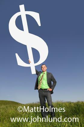 Image of a man holding up a giant money symbol, a giant white dollar sign. The sky is blue and the grass he is standing on is green. Unique and interesting advertising pictures for small businesses.