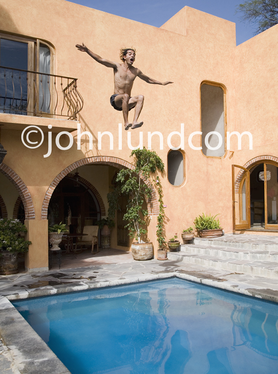 A man makes a splash as he jumps from a balcony into a pool exhibiting risky behavior.