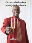 Picture of a man offering up a glass of bubbly champagne.  An African American man is holding out a glass of champagne toward the camera.  The man is wearing a burnt orange dress shirt and a tie.