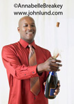 Picture of a man popping the cork on a champagne bottle. An African american man has just popped the cork on the champagne bottle and the cork is in mid air flying away. Smiling man opening champagne bottle. Advertising photos of celebrations.