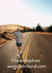 Picture of a middle aged man with gray hair jogging down the middle of a road alongside the double yellow lines.  He is wearing blue shorts and a gray sweat shirt and white running shoes.