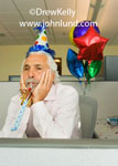 Photo of a dejected looking man wearing a funny party hat and holding a noise maker in his mouth.  He is resting his face in his hands and looks bummed out. Colorful party balloons in background.  Sad man pics at office cubicle party.