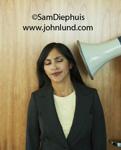 Pictures of Job Stress - Image of an employee being yelled at through a megaphone held right up close to her ear. Irritating boss photos. Ad pics.  Screaming boss pictures for ads. Funny business stock photos. Pics of irritated woman worker.