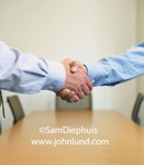 Picture of a firm solid handshake between two white men. No sloppy handshakes here. Two hands and arms only shaking hands with a solid firm grip.  Pics of great handshake grips for ads.