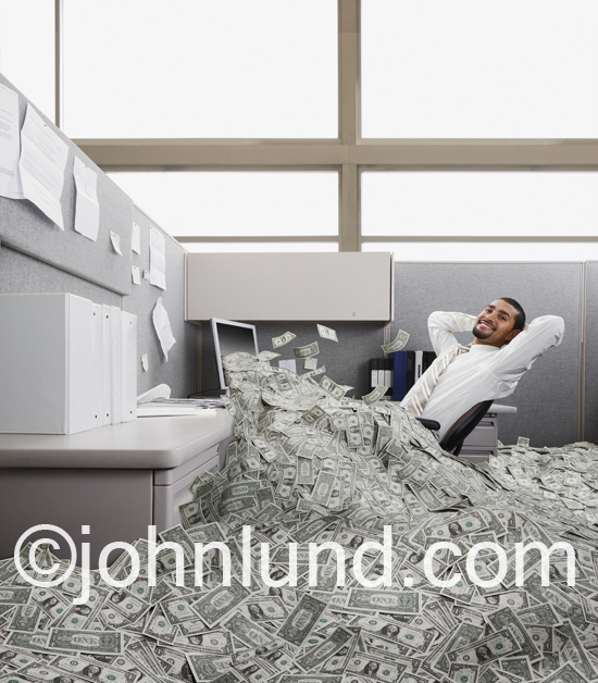 An Hispanic businessman leans back in his office cubicle as a vast sum of dollars pours out of his computer monitor showing success in a humorous