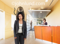 Photo of a woman in a corporate reception area with a monkey or Baboon on her back.