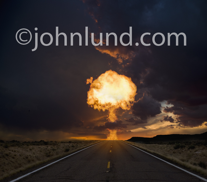 Picture of a fiery mushroom cloud exploding over the distant horizon of a long road stretching ahead, an indication of disaster ahead.