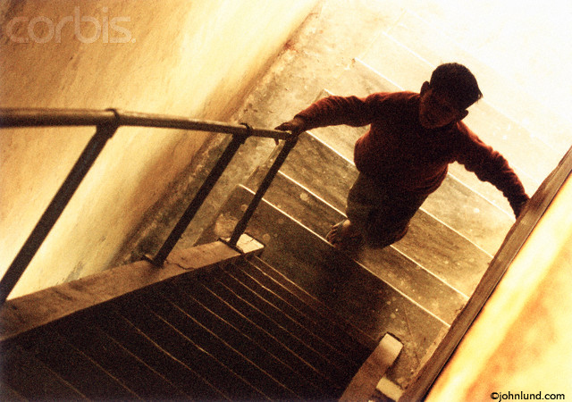 Picture of a boy climbing stairs. The child is in the shadows with a bright light behind him. Silhouette of a curious boy doing some exploring.