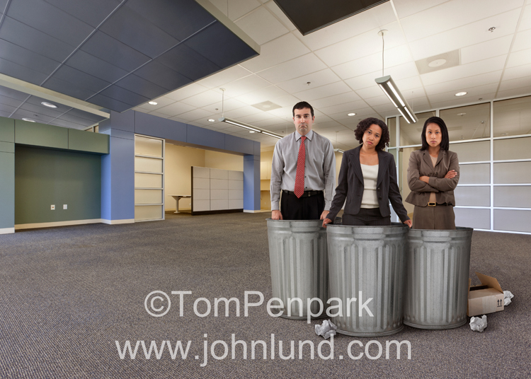 Three discarded employees stand in garbage cans in this photo about outsourcing, lay offs, and employment issues.