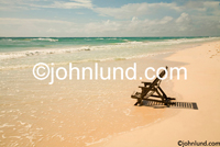 Stock picture of a lounge chair in the surf - tropical island paradise luxury spa photos about vacation and getting away from it all.