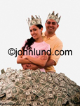 An Hispanic couple, wearing crowns fashioned from dollars, stand in a huge pile of money. He is behind her with his arms around her. She has long hair and her arms are crossed in front of her.