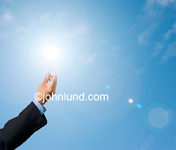 Stock shot of a man's hand holding a light bulb in front of the sun to indicate solar power, solar energy and sustainable energy.