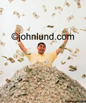 Picture of an excited Hispanic man stands in a huge pile of cash with more money in each upraised fist. Money is floating down from the sky. Man is wearing a yellow shirt.  Freedom from debt photo.