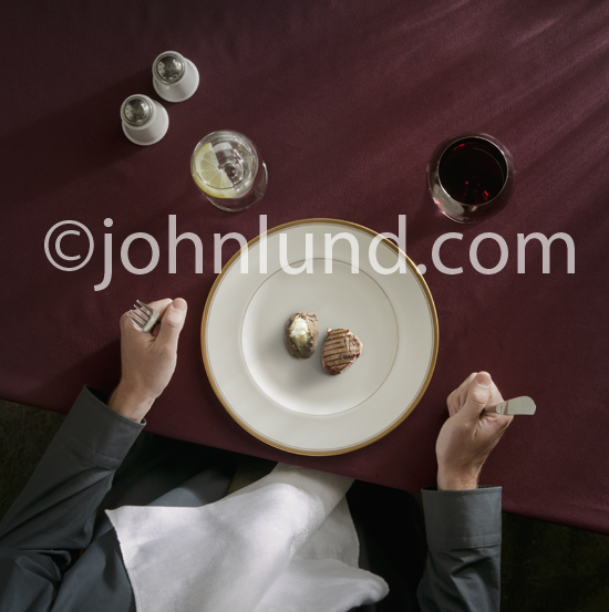 Concept stock photo of a man seated before a diner plate with a tiny portion of meat and potatoes.