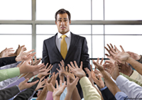 A mixed race businessman stands surrounded by a multitude of hands reaching out to him in need in an image of being overwhelmed.