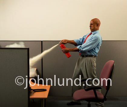 Funny photo of a businessman putting out a fire at his desk.