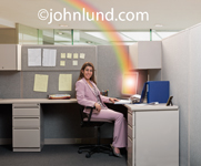 A woman sits in her cubicle with a rainbow ending in her computer in a photo depicting business success.
