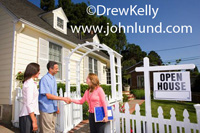 Picture of an open house. Red headed female real estate agent shaking hands with a couple interested in buying a house. Open house pictures for real estate advertising.