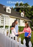 Photo of a couple purchasing a home shaking hands with a woman real estate agent. The man has his arm around his wifes shoulders. Two story home, white, with shrubs and a lawn. Pictures of people buying a house.