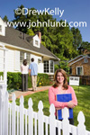Picture of a female real estate agent selling a home to a white couple. The agent is standing behind a white picket fence with an armload of paperwork.  She is smiling at the camera. In the background the home buying couple is looking at the new home.