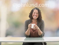 Picture of a woman relaxing out doors with a cup of coffee or java against a background of out of focus fall foliage.