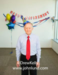 Picture of a senior executive standing in the office in front of party decorations on the wall for his retirement party. Man is wearing bright red neck tie.