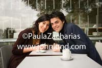Romantic picture of a Latino or Mexican couple having expresso together in a cafe.  Happy couple in love posing for a photo.  The couple is leanging forward touching their heads together.