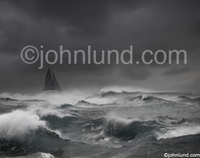 Picture of a sail boat in an ocean storm with dark clouds overhead and wind blown white caps all around. The boat is difficult to see in the darkness of the raging storm.