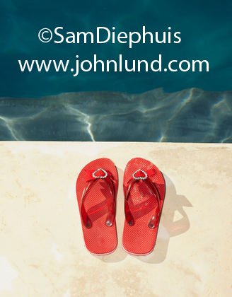 A sign of summer, a pair of bright red flip flops with rhinestone heart decorations are sitting on the side of the public swimming pool.