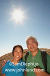 This happy senior asian couple are on a day hike. He is wearing a backpack and has a walking stick. He has his arm around her. He has gray hair and she has black hair.
