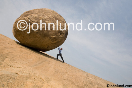 Concept stock photo of a man pushing a huge boulder up a steep hill like Sisyphus, the greek God with an endless and pointless task.