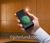 Picture of a man's hand holding a mobile smart phone with a techno-bomb, fuse burning, visible on the screen.