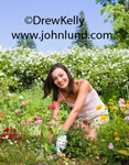 Picture of a happy woman doing gardening work on her flower garden at home on a bright warm sunshiny day.  She is wearing a pink blouse and gardening gloves.  The young adult woman is surrounded by beautiful flowers growing in her garden.