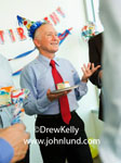Pictures of a senior executive or businessman holding a paper plate with a piece of cake and wearing a funny party hat at his retirement party. Pictures of people having an office party. Office party pics for ads.