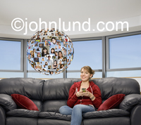 A teen girl engages in text-messaging with her social networking media while sitting on a couch next to a sphere composed of pictures of her friends and family.