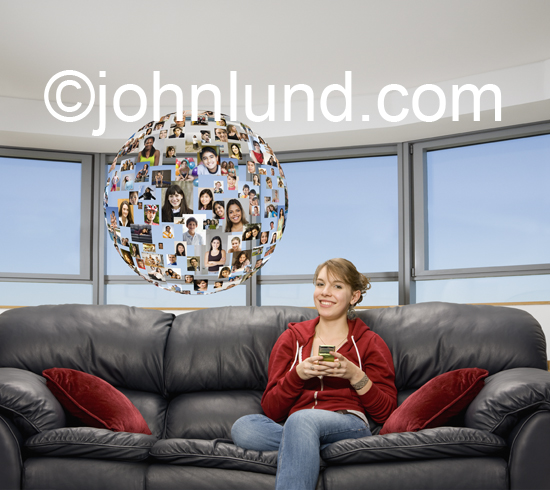 A teen age girl uses her cell phone texting to her social network which is symbolized by a sphere of portraits (sphere of influence) of her friends and family that hovers next to her.