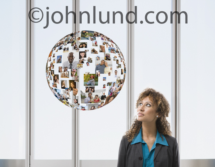 A woman examines her social media world in the form of a sphere of pictures of family, friends and business acquaintances.