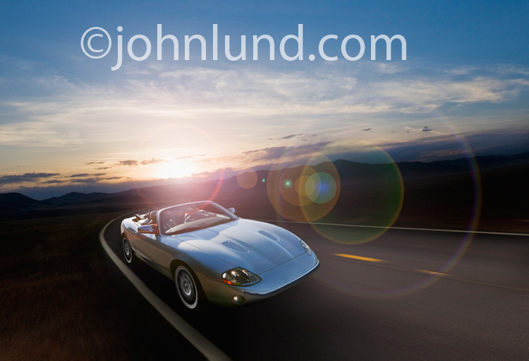 A beautiful silver convertible sports car speeds in solitude down a long empty road at sunset in a picture of success, freedom and the way forward.