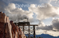 A steam locomotive is speeding over a railroad trestle that has collapsed in this mountain train scene of impending disaster.