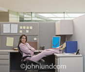 A happy, successful woman leans back in her chair, feet on her desk, in her cubicle and smiles confidently.