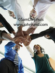 Teamwork in the office is the theme of this stock photo for advertising. One for all and all for one.  Multi-ethnic group of office workers stacking their hands up one over the other. Picture of employees working together. Ad pics.